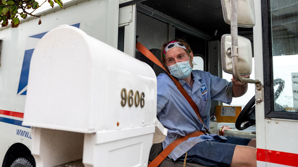 A USPS worker wearing a mask puts envelopes in a mailbox while driving past