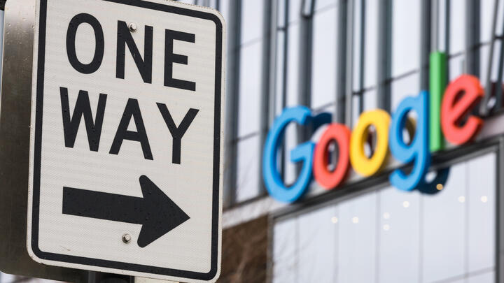 A one way sign next to a Google sign
