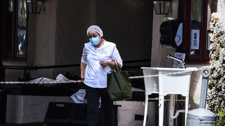 A staff member outside Fair Havens Center nursing home in Miami Springs, Florida, in May 2020. Fifty-four residents of the nursing home have died from COVID-19. Photo: Chandan Khanna/AFP via Getty Images.