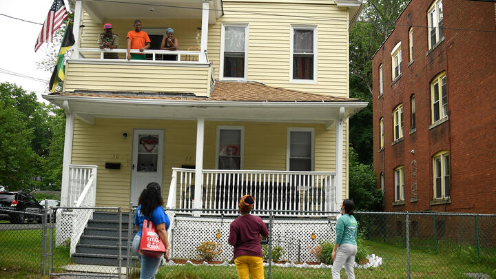 Hartford Public Schools Superintendent Leslie Torres-Rodriguez (bottom right) and other school leaders talk with a family on their second-floor porch in the district in June 2020. AP Photo/Jessica Hill.