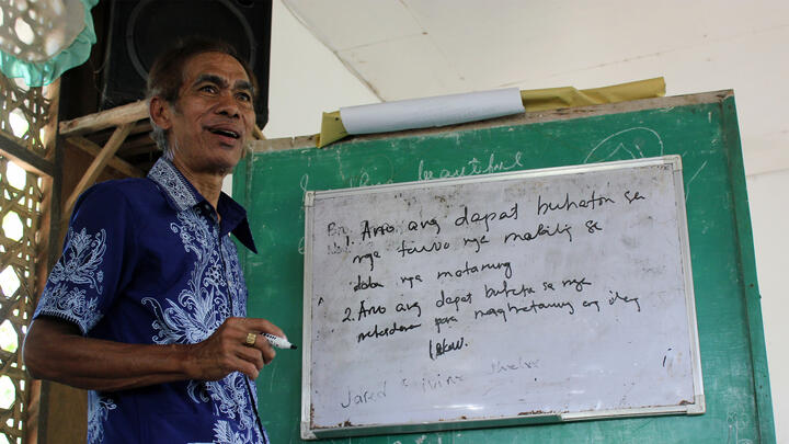 A speaker in front of a whiteboard in the Philippines