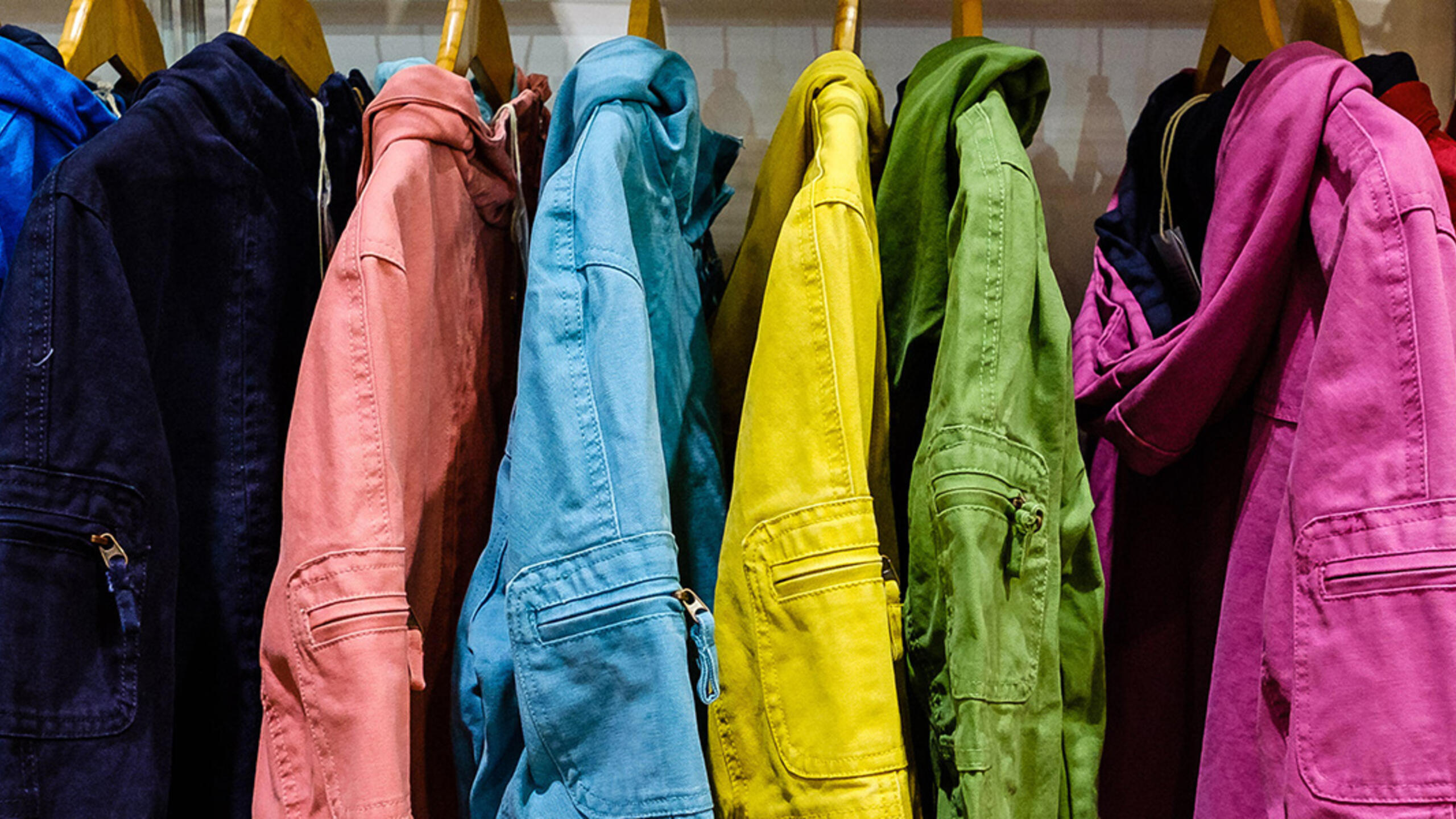 A coat rack of jackets of different colors.