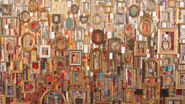 An abstract mixed media assemblage including picture frames of various colors and shapes