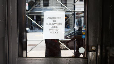 "The door to a business with a sign reading ""Closed due to cororavirus until further notice"""