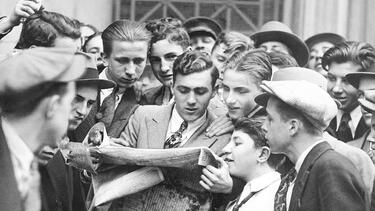 Messengers from brokerage houses crowd around a newspaper after the stock market crash on October 24, 1929. Photo: by Eddie Jackson/NY Daily News Archive via Getty Images.