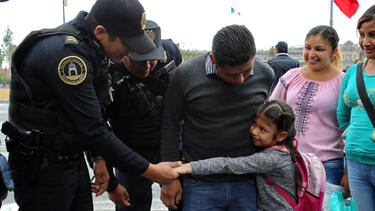 Mexican police officers greeting a family