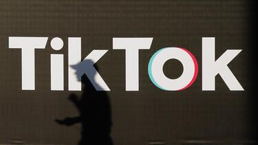 A shadow of a person walking in front of a TikTok sign