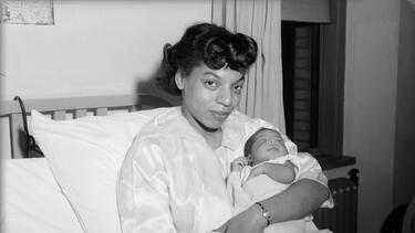 A black and white photo of a Black woman holding a newborn baby in a hospital ed