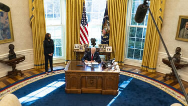 President Joe Biden signing an order at the desk in the Oval Office