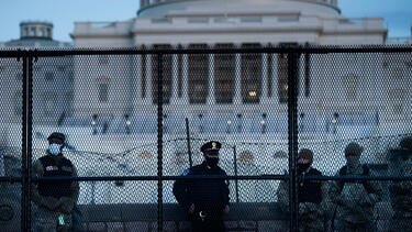 Police and members of the National Guard behind a fence outside the U.S. Capitol on January 7, 2021.