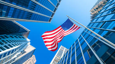 An American flag surrounded by office towers