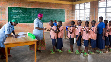 Students receiving a deworming treatment at a school in Rwanda.