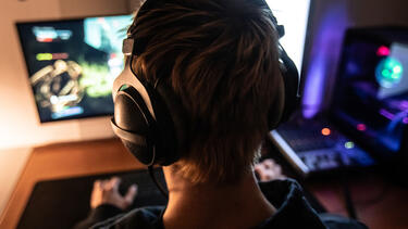 A young man wearing a headset playing a video game, seen from behind