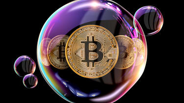 Bitcoins floating in a bubble on a black background