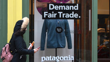 "A Patagonia store with ""Demand Fair Trade"" and ""Buy Less, Demand More"" in the window."