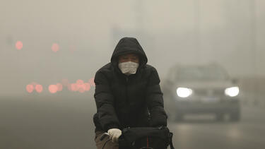 A cyclist in Beijing on a day of heavy pollution in December 2015.