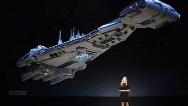 Anne Morrow Johnson standing in front of an image of a Star Wars starship