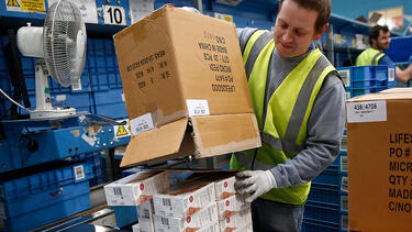 "A warehouse worker unpacking a box labeled ""Made in China"""