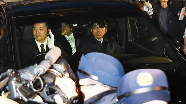 Media surround a car carrying Carlos Ghosn after he was released on bail on March 6. Photo: Jun Sato/WireImage/Getty Images.