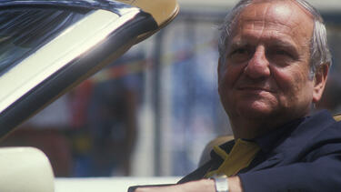 Lee Iacocca at the steering wheel of a car