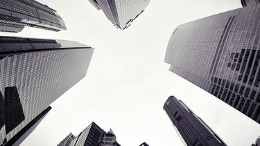 A view upwards with tall buildings surrounding