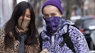 Two women wearing cloth masks color-coordinated with their clothes