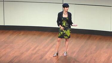 Zoe Chance lecturing from the front of a classroom gesturing with one hand