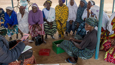 An NGO representative meeting with women in a village in Burkina Faso