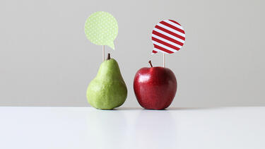 A green pear with a green speech bubble and a red apple with a red speech bubble