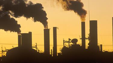 Factory smokestacks at sunset