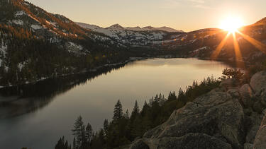 The sun rising over mountains and a lake