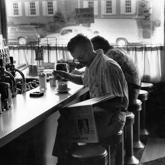 A man reading a newspaper at a diner